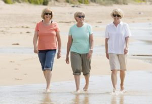 3 women walking down the beach in Rockland, Maine