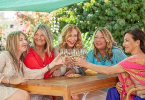 5 women sitting outside drinking wine in Maine