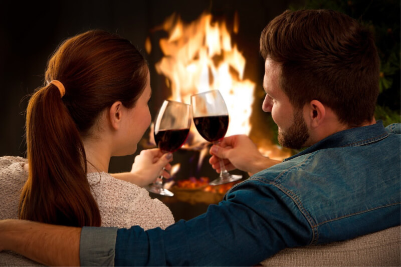 couple relaxing with wine in front of a fireplace