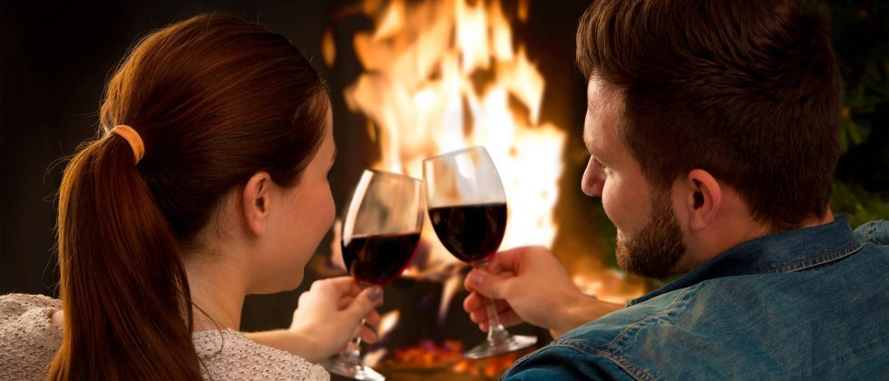 Couple toasting red wine in front of fireplace