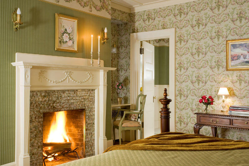 Romantic guest room with sage green walls and a raoring fire in the fireplace