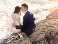 Couple sitting on the rocks at the edge of the ocean on their wedding day with a bouquet set beside them