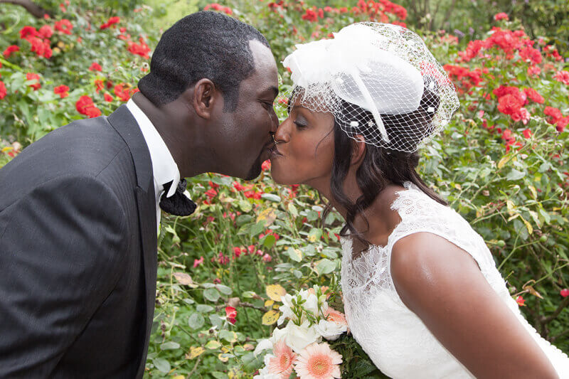 African American couple kissing in the rose garden on their wedding day