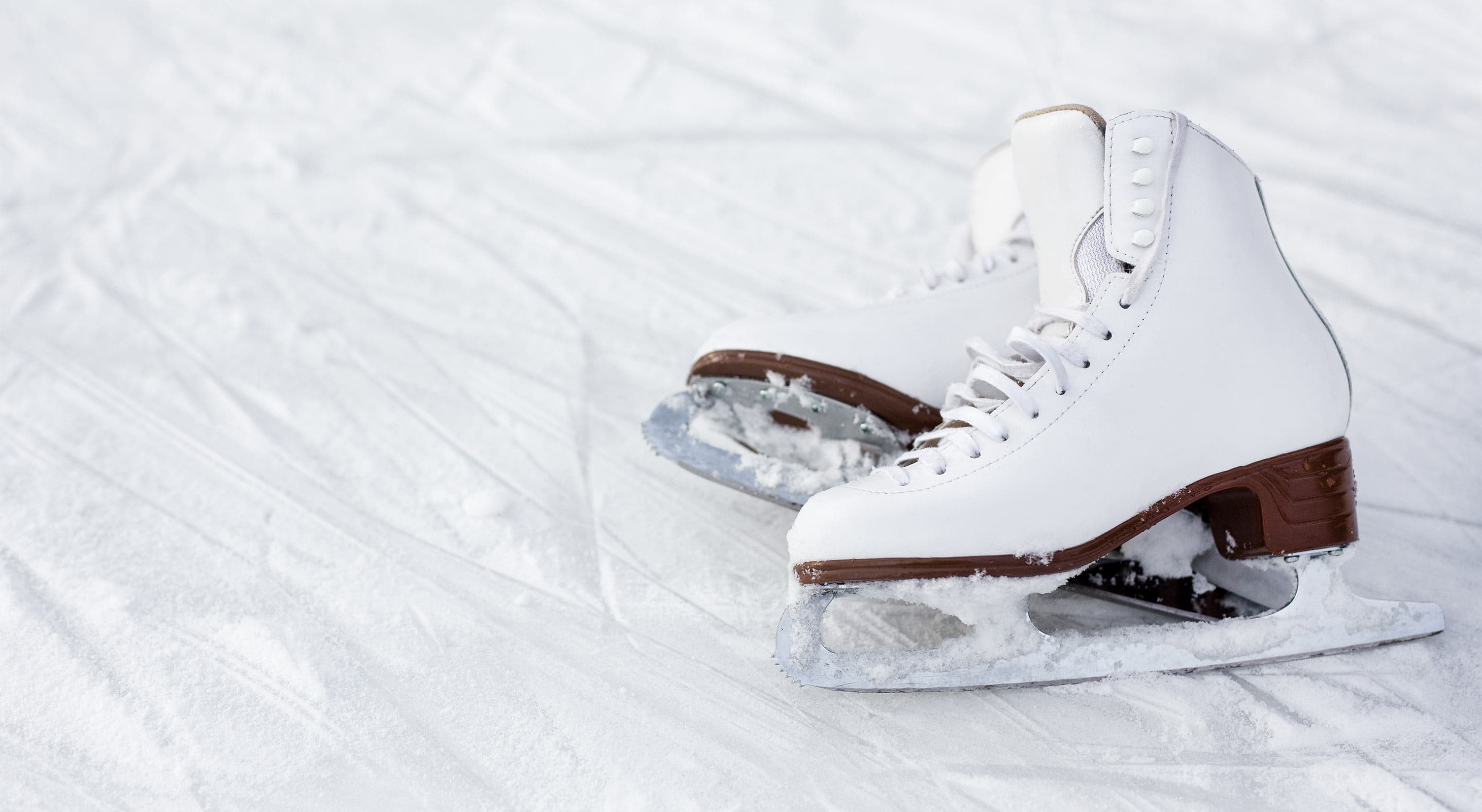 Pair of white ice skates lying in the snow