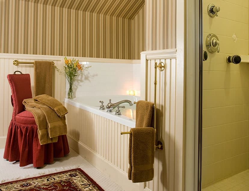 Bathtub with soft furnishings, chair, and towels next to shower