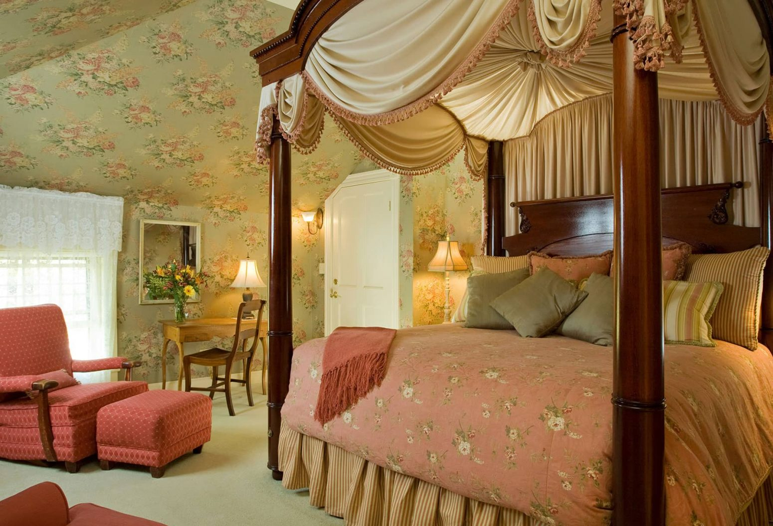 Tall, luxurious Four-poster bed by comfortable sitting area in Room 12
