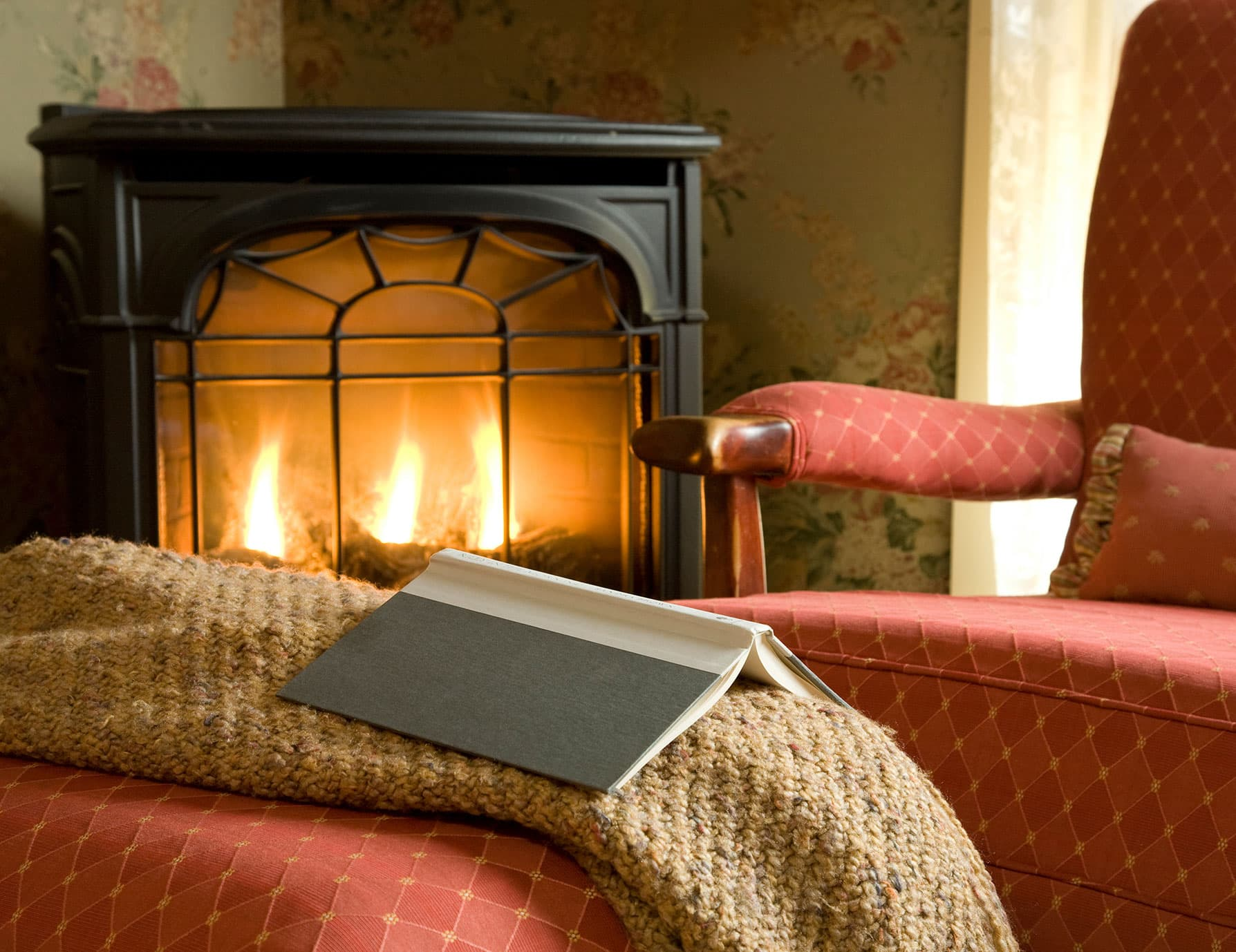 Book on ottoman by warm gas fireplace