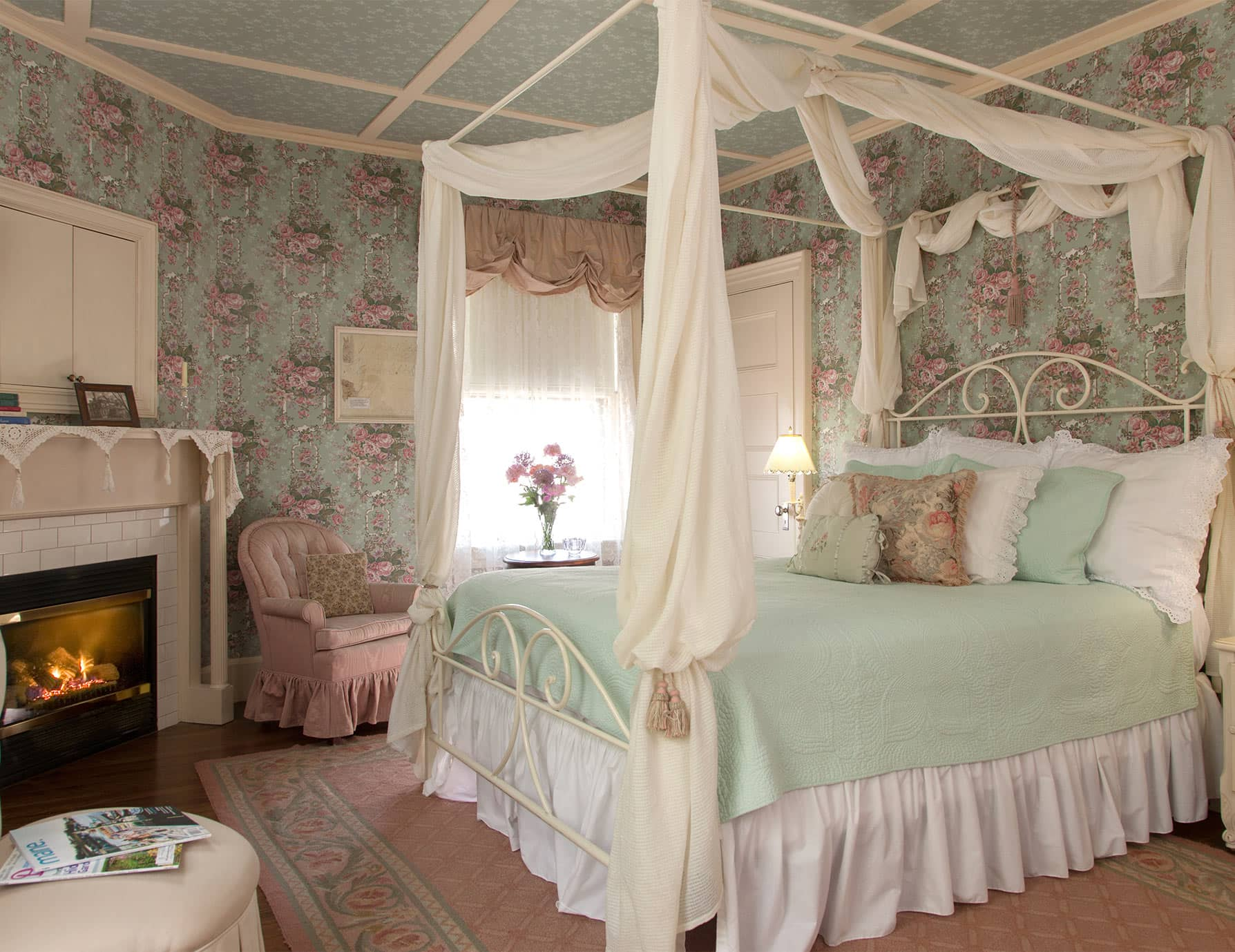 Comfortable pink bed with drapery across from fireplace in Room 4