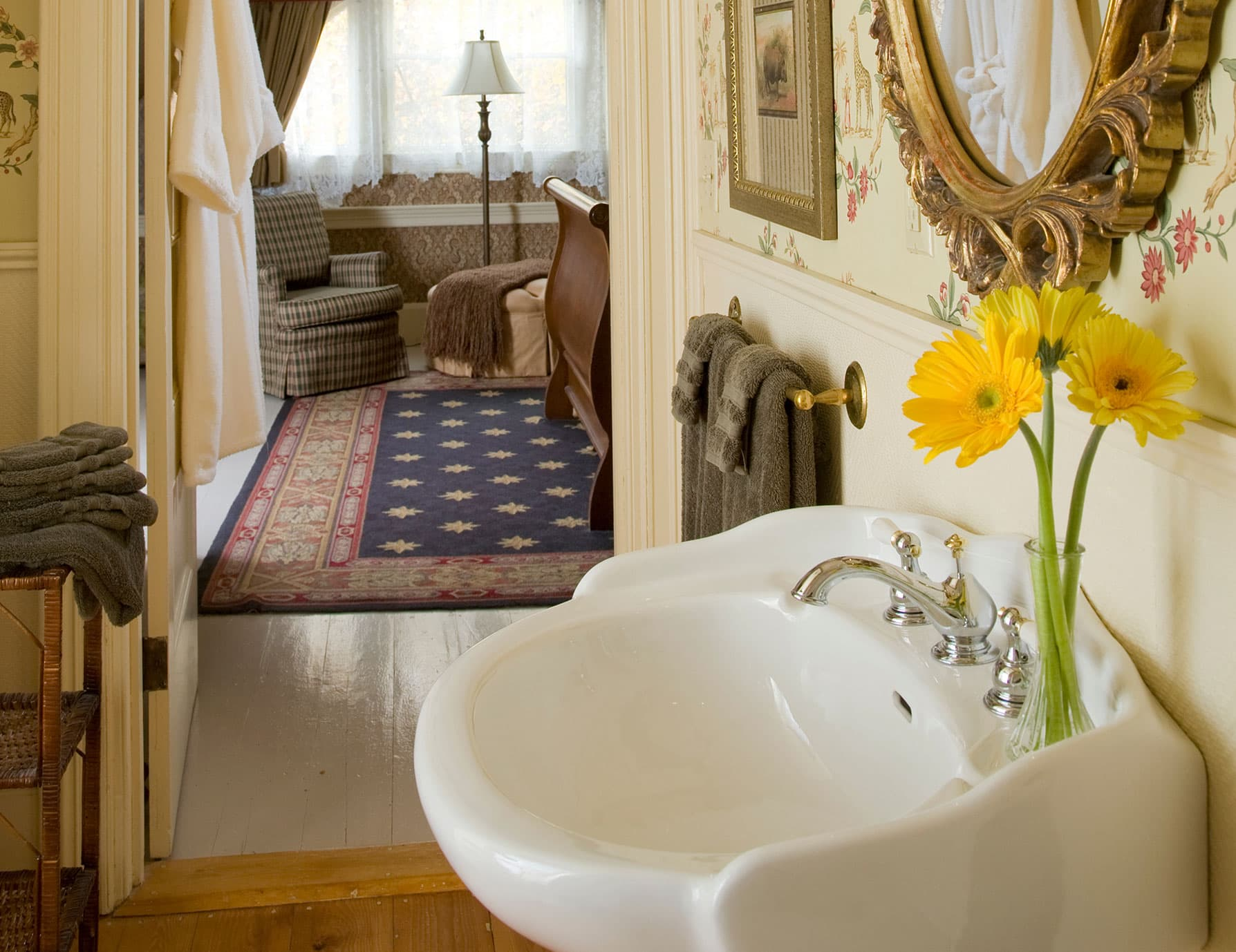 Bathroom sink and mirror with view of sitting area down the hall