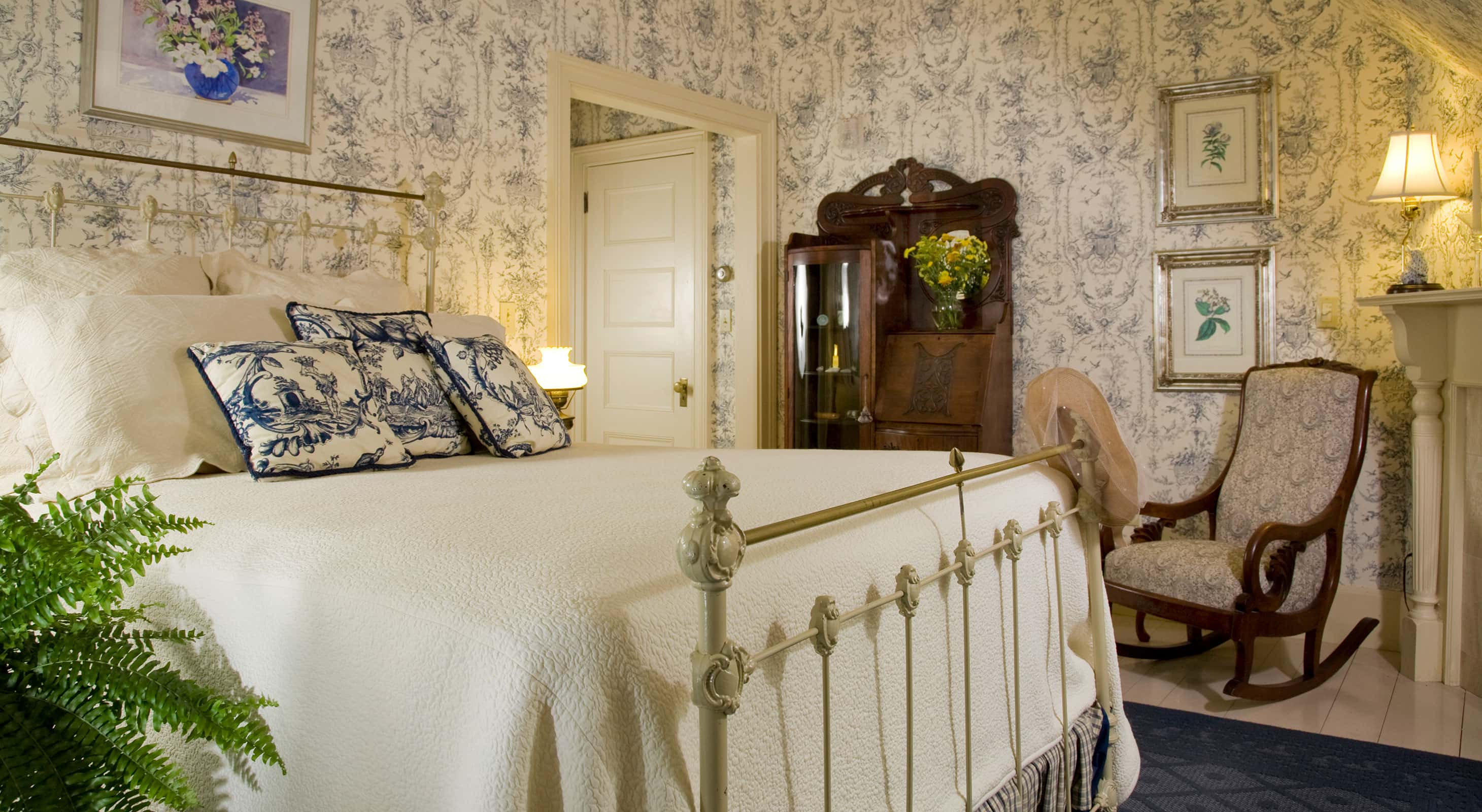 Antique-style metal bed across from ornate wooden stand in Room 7