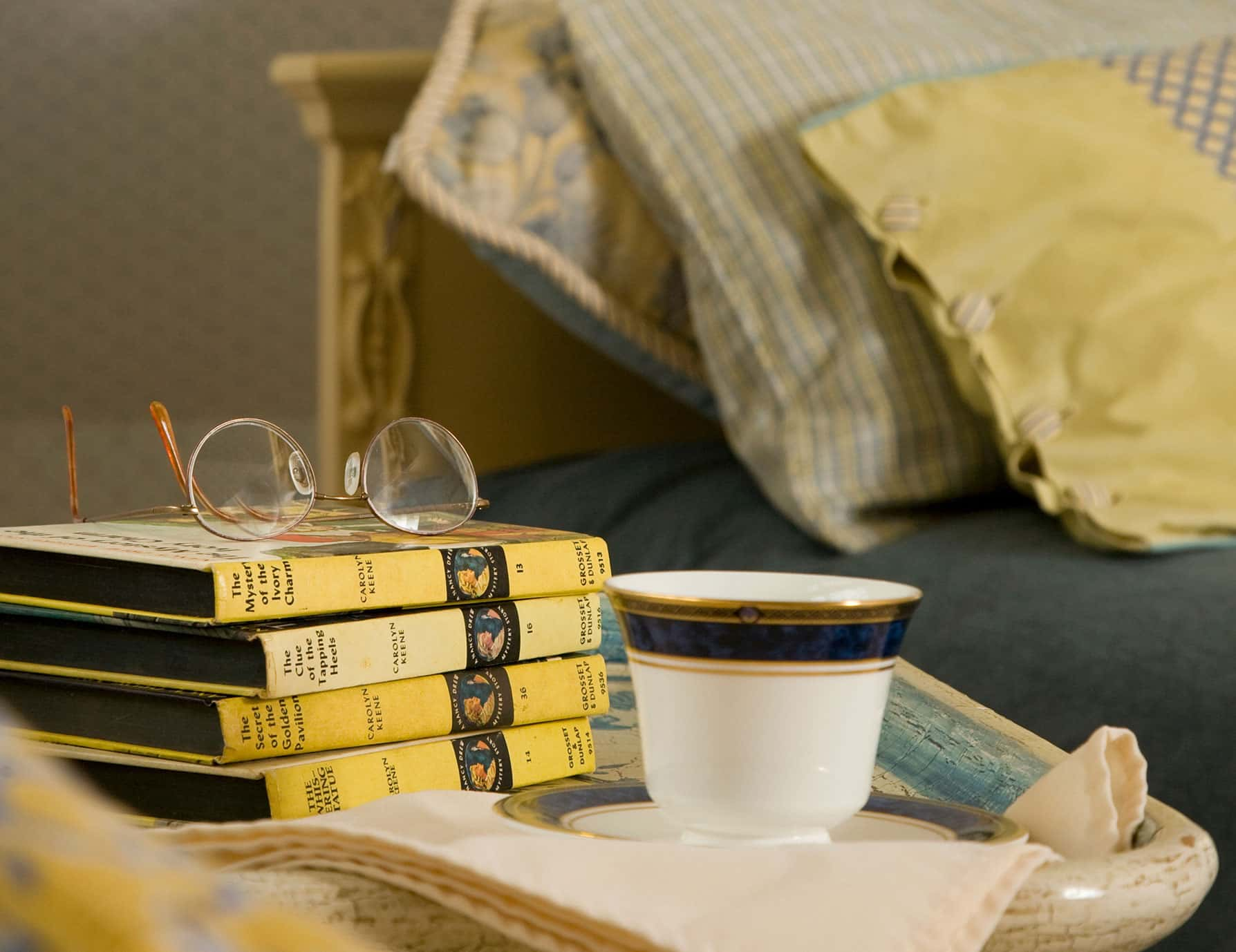 Stack of books with coffee cup on nightstand