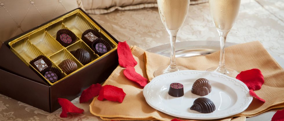 Pair of champagne glasses with plate and tray of delicious chocolates