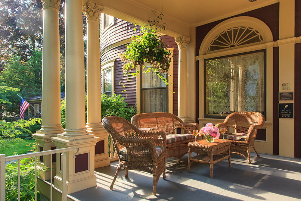 wicker seating on porch with hanging greenery