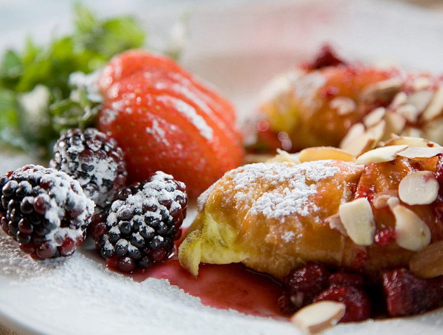 Breakfast pastry and fruit dusted in powdered sugar