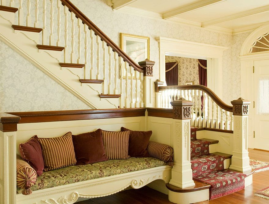 Bench sitting area with pillows under staircase