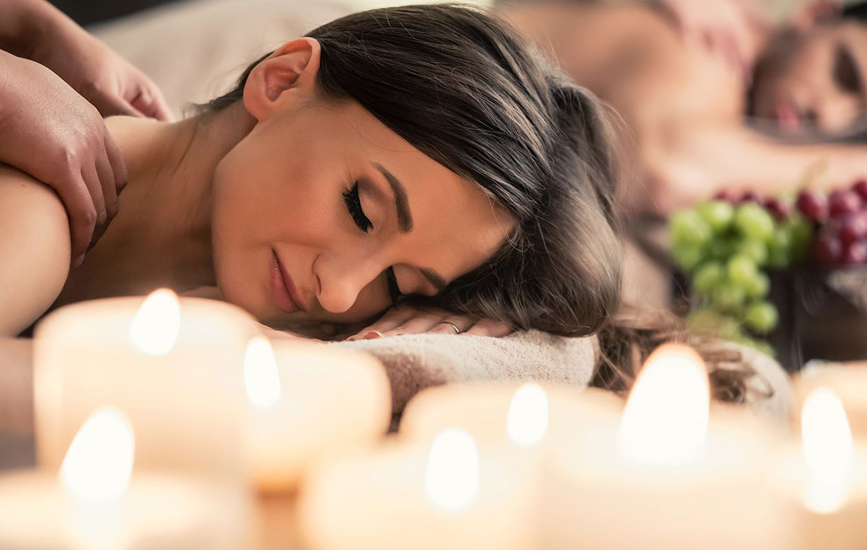 Couple receiving massage near candles
