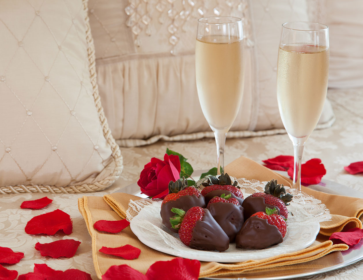 Chocolate-dipped strawberries with rose petals and sparkling cider