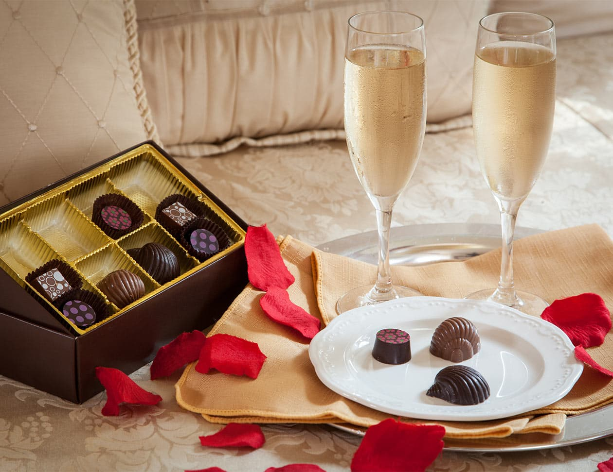 box of chocolates and 2 flutes filled with champagne