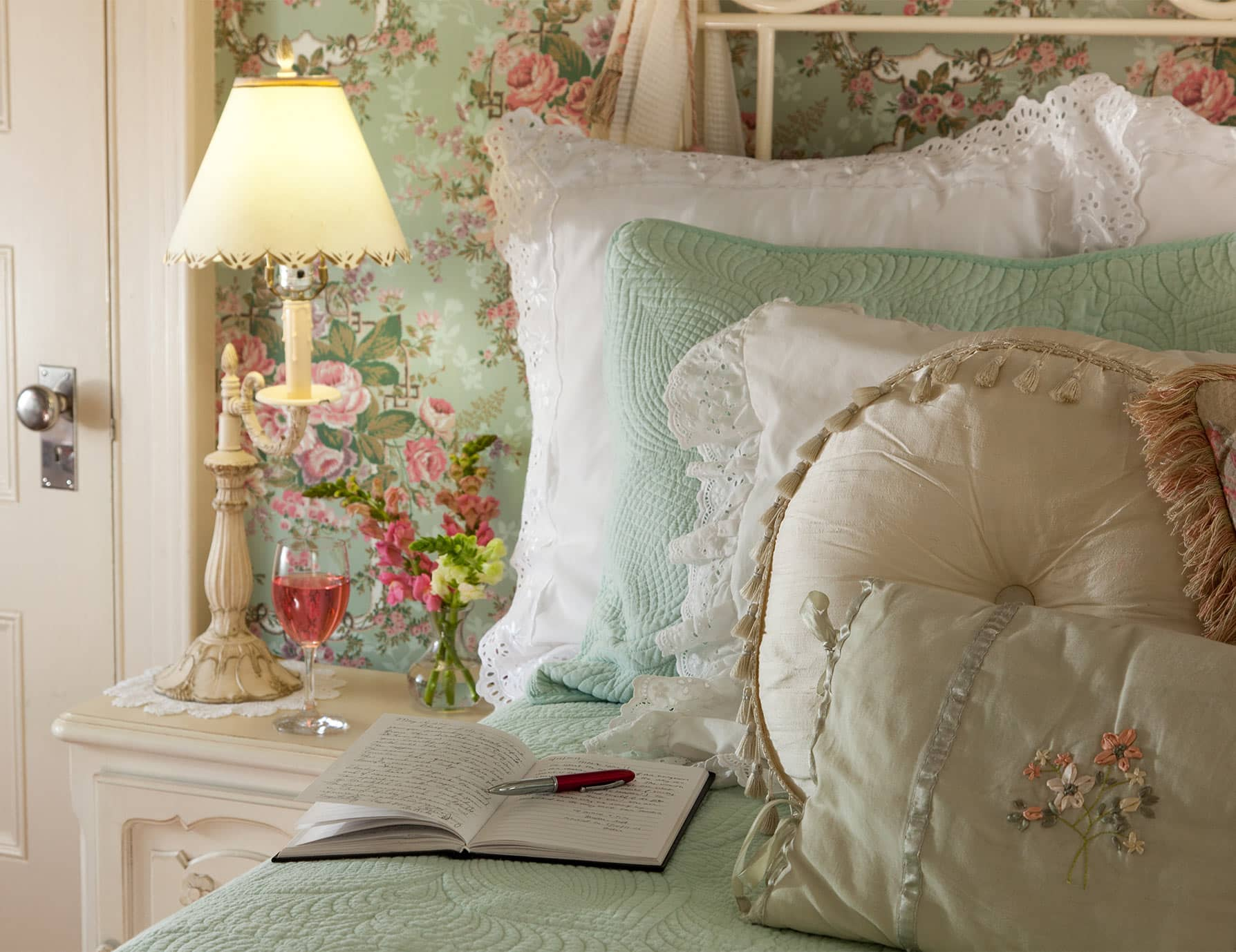 Lamp and wine on nightstand by bed with many pillows and journal