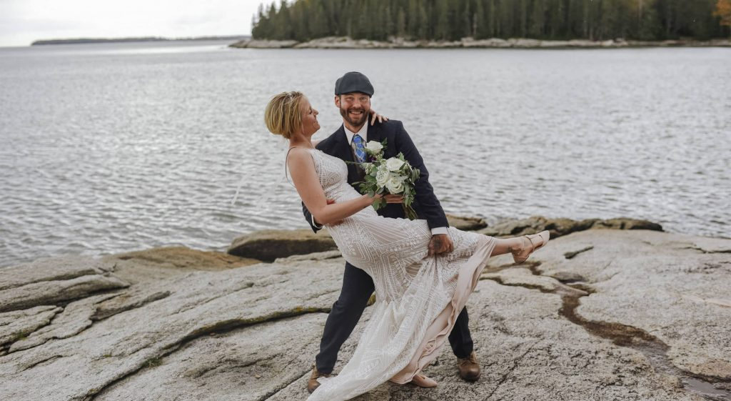 Elopement couple on rock in front of water