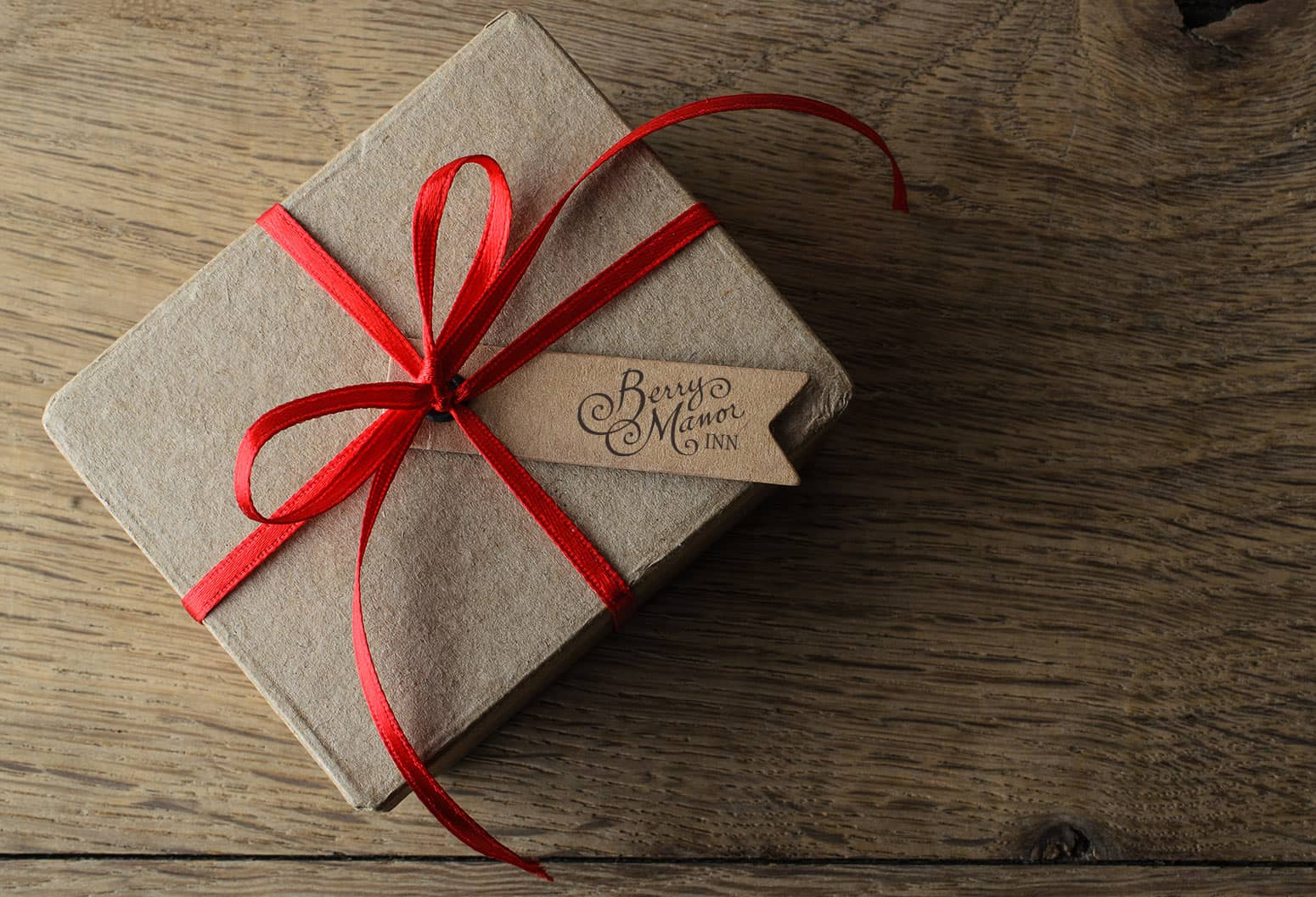 Gift Box with red bow and Berry Manor Inn logo