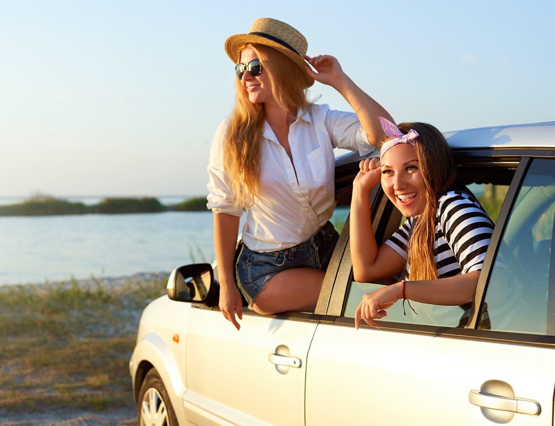 Two younger girls in a car enjoying a getaway