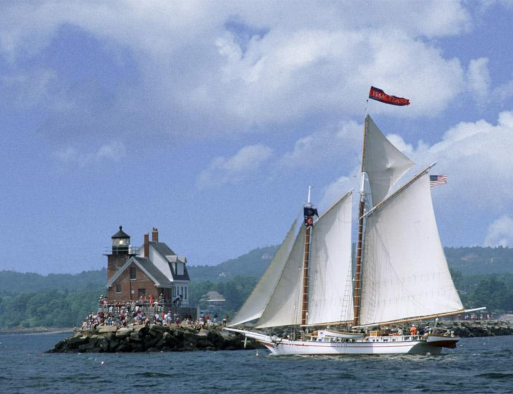 White schooner with sails aloft on blue sea in front of lighthouse on a rocky perch with mountains in the background lighthouse