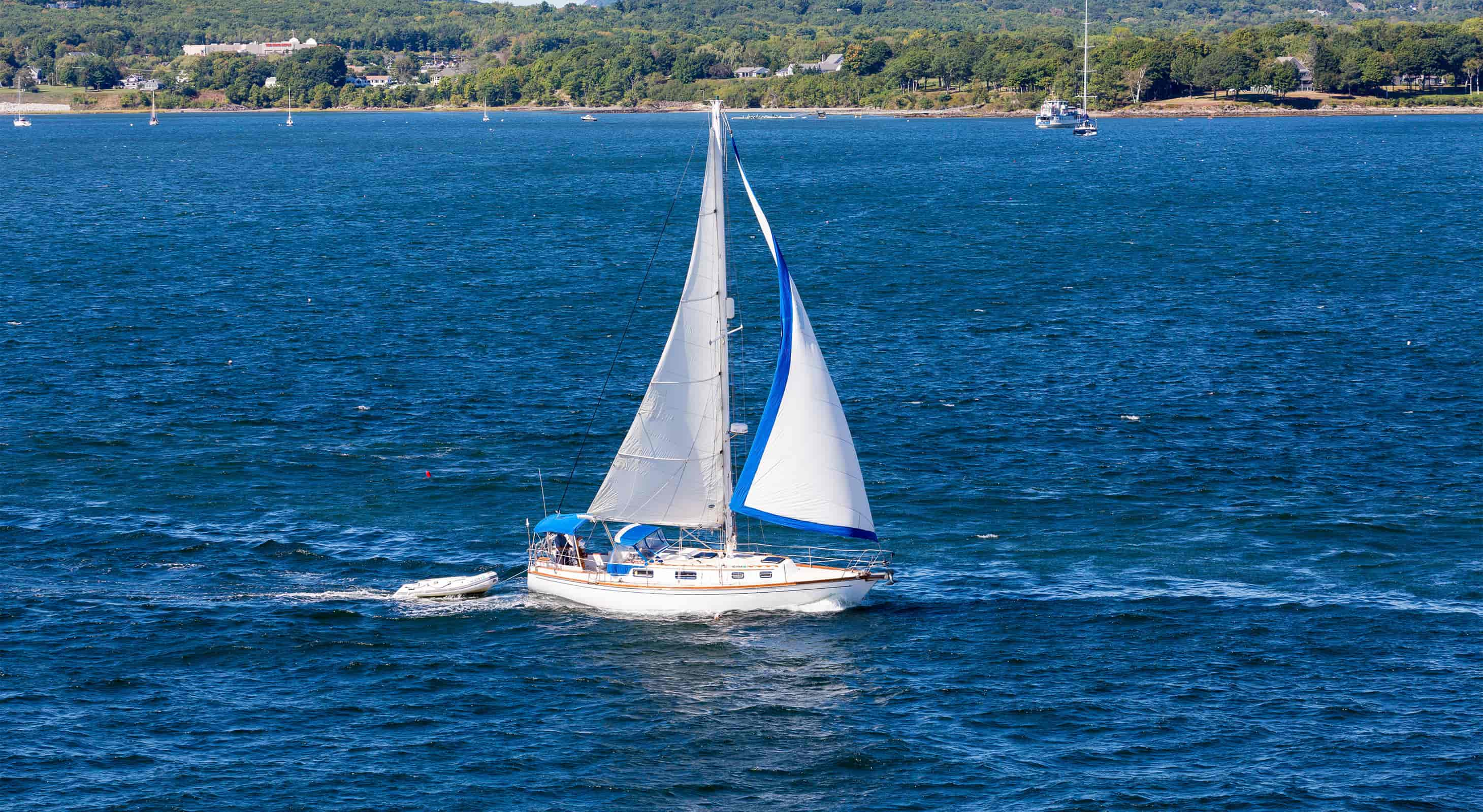 White sailboat with white sails on a blue ocean