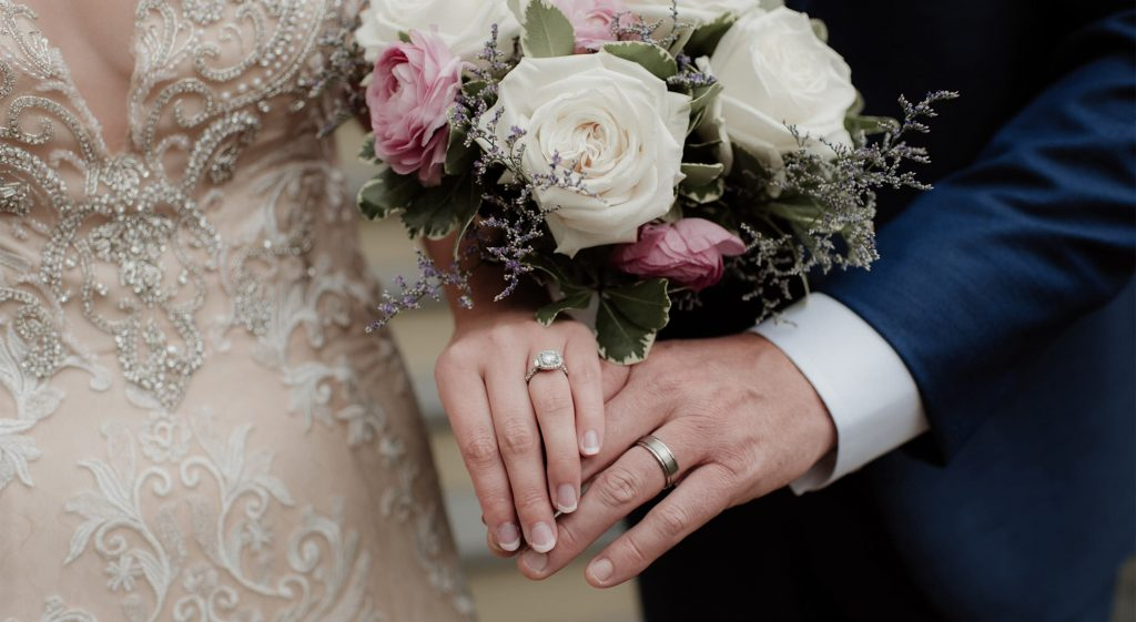 Hands of the Bride and Groom along with a flower bouquet at their petite wedding