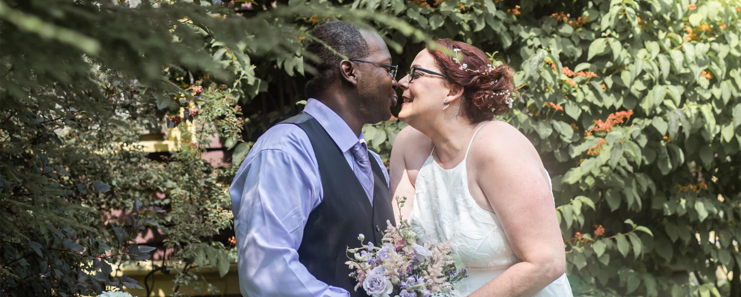 Bride and Groom about to share a kiss in the garden