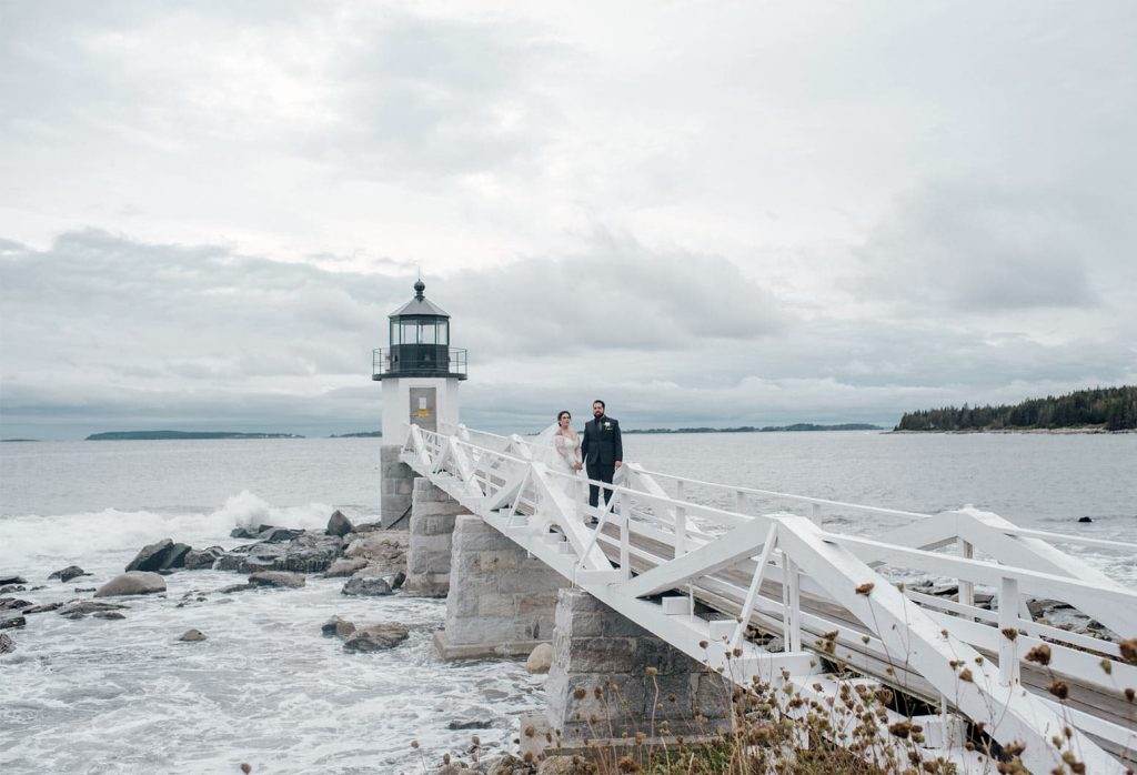 Elopement couple on the pier by a lighthouse