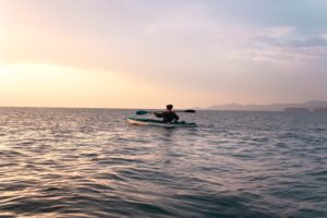 Sole kayaker at dusk paddling on the ocean with a pink and yellow tinged sky