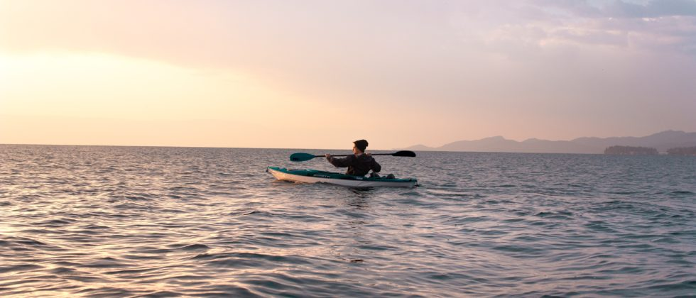 Kayaking at dusk with a pink and yellow tinged sky