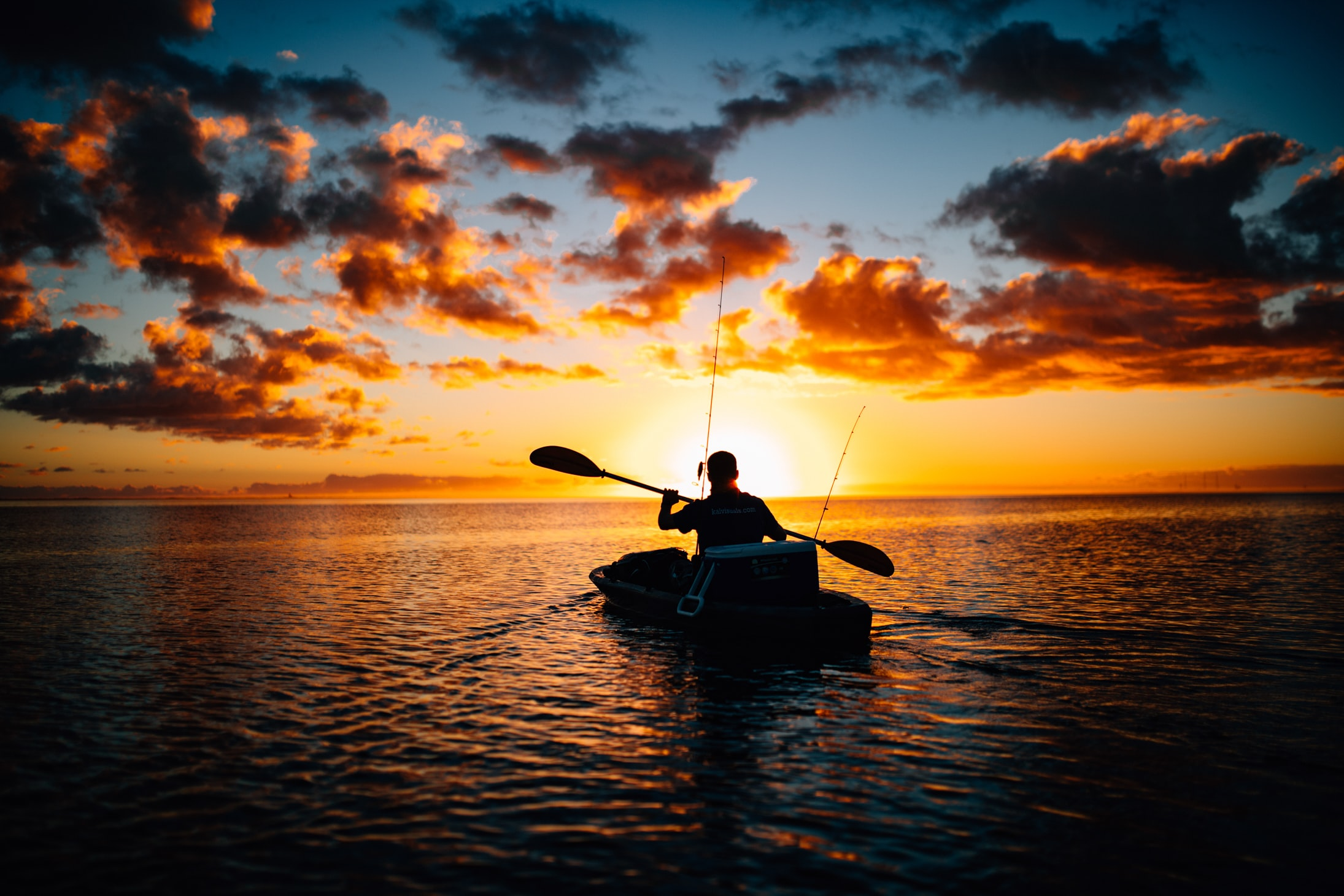 Silhouette of a man kayaking at sunset amidst a brilliant sky of deep gold, orange and red