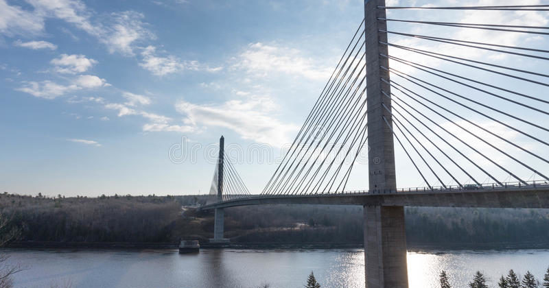Two granite towers with cable stay suspension cables across the Penobscot river with blue sky in background