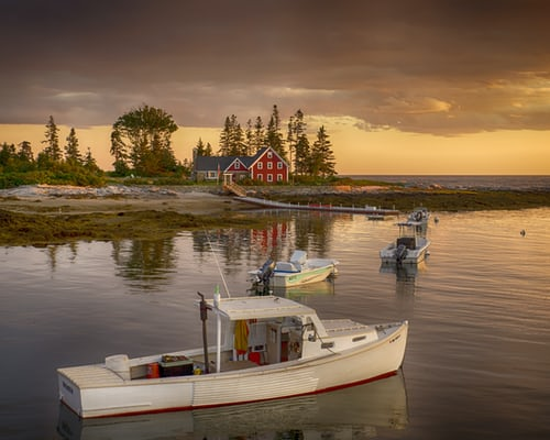 White lobster boat in harbor with shoreline in background dwith red building