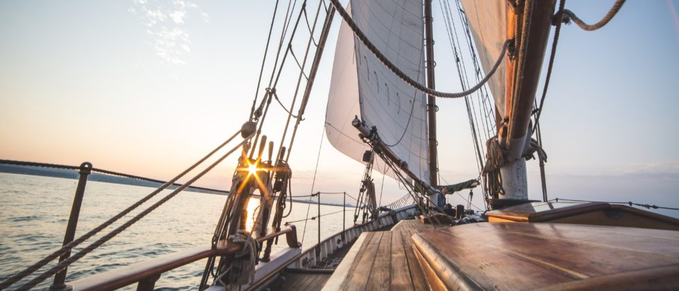 View from the deck of a sailboat soaring through the open water with full white sails