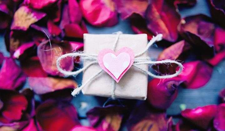 square white box with pink heart on top and rose petals all around