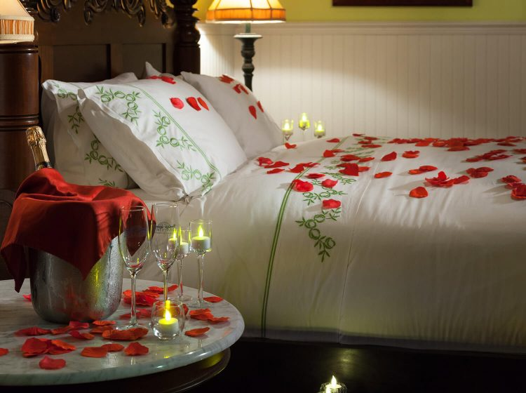 Red rose petals strwn across a bed with with down comforter.
