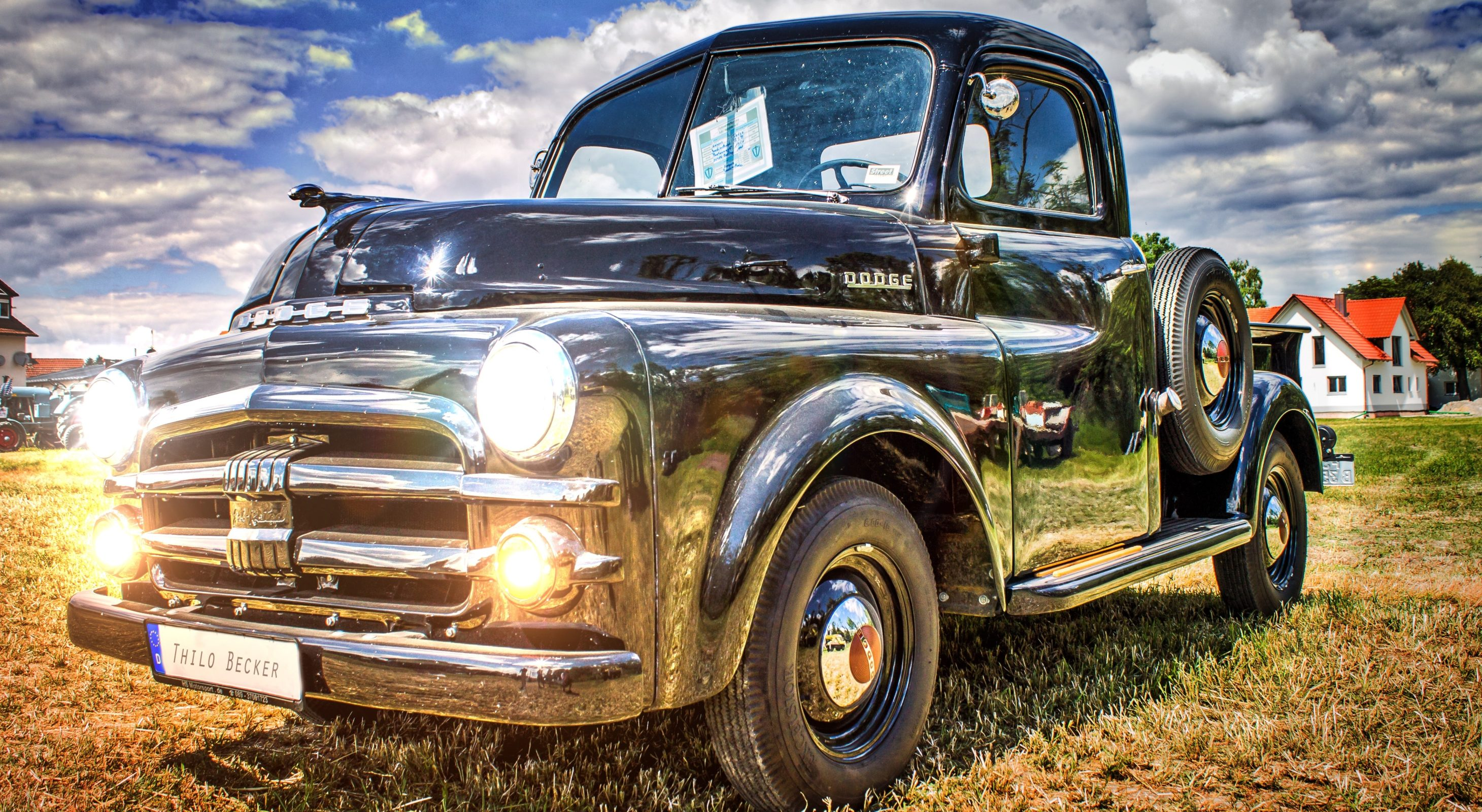 vintage silver truck with headlilghts on on green grass