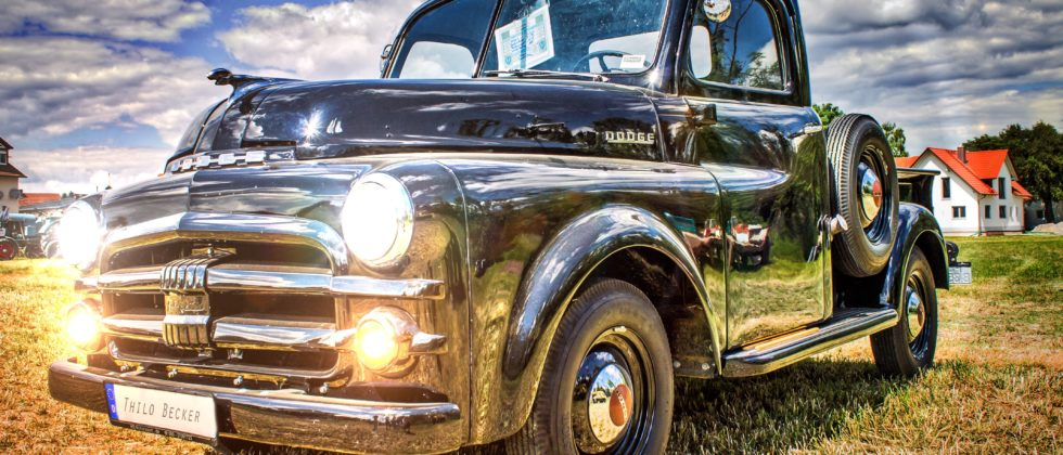 vintage truck parked outside amidst blue skies with white clouds