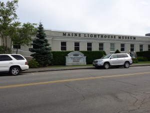 long white building with white SUV in front and green evergreen tree