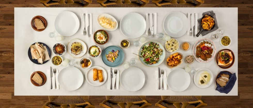 Wood table topped with plates of farm to table food