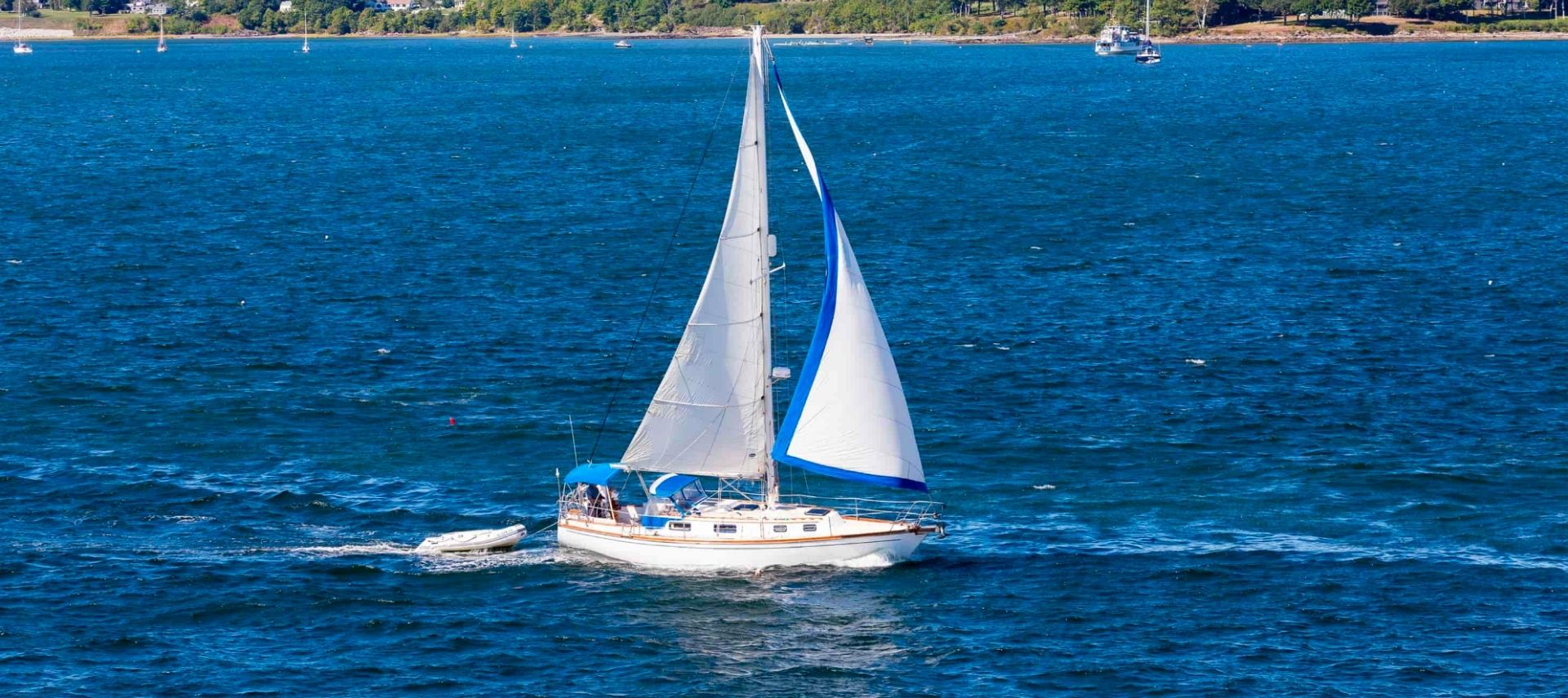 White sailboat with white sails sailing in the open blue water