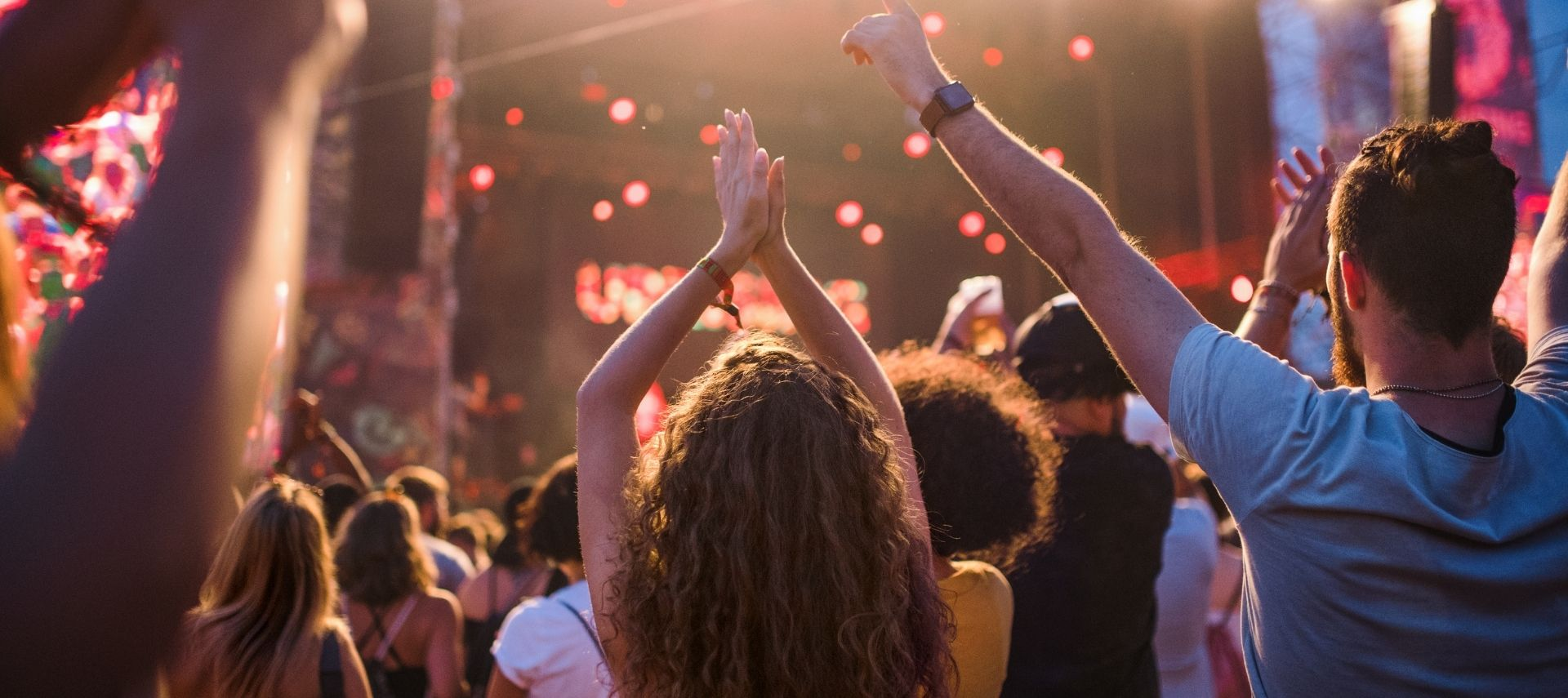 Outdoor concert with people raising their arms to the music