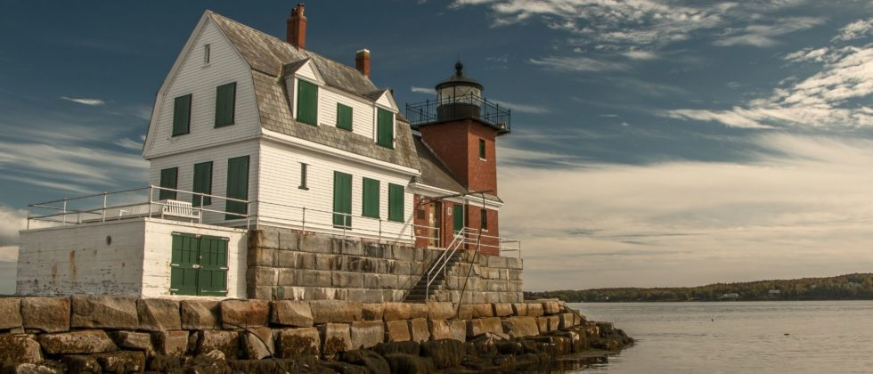 Beautiful red lighthouse with attached two-story white house on a rocky outcropping overlooking the water